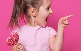little girl holding lollipop and pointing with an excited smile