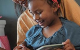 picture of a little girl and a mother reading together from a book, smiling