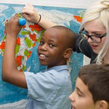 In this photograph, a young boy of African decent is stood in front of a map of the world, holding a turquoise PENpal, a talking pen device developed by Mantra Lingua that enables him to listen to and add sound to books, drawings and other objects.